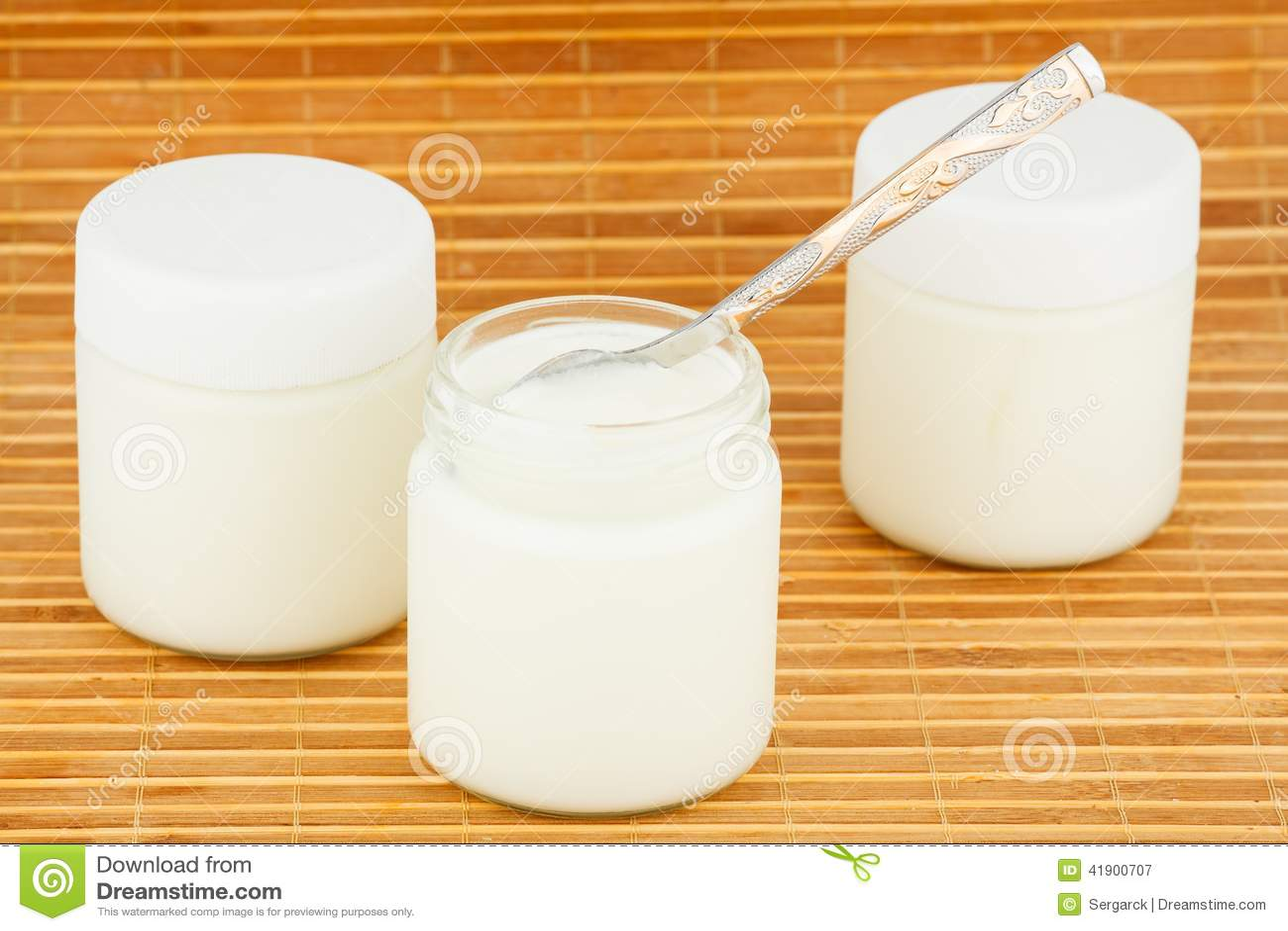 Tres tarros con el yogur casero en una estera de la paja