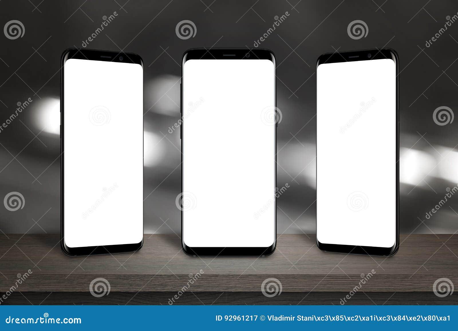 Tres teléfonos móviles con la pantalla para la maqueta en la tabla