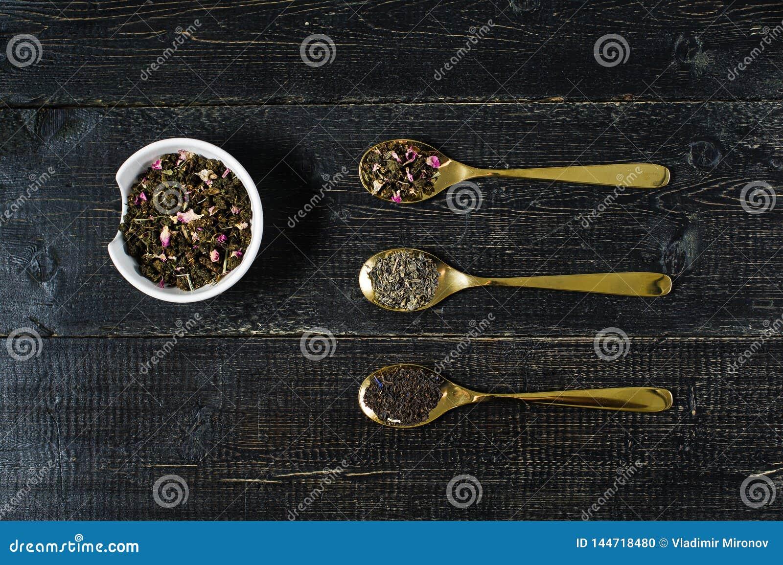 Tres tipos de té en las cucharas - verdes, el negro y Rooibos