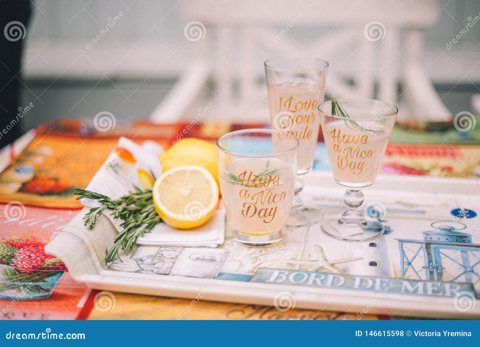 Tres vidrios con las bebidas de la fruta c?trica en una bandeja Está después el limón y el romero cortados