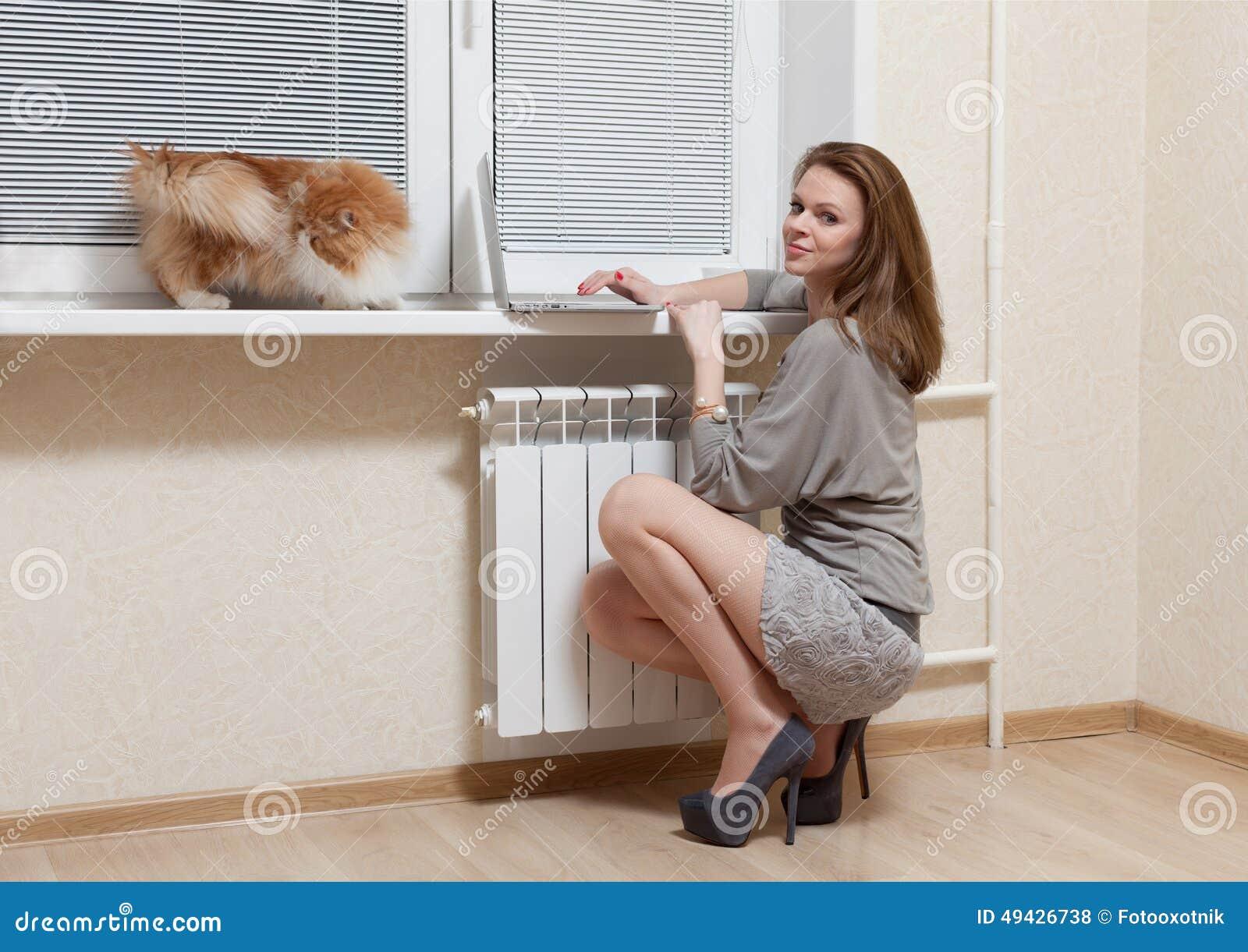 Trevlig blondin på ett fönster med bärbara datorn