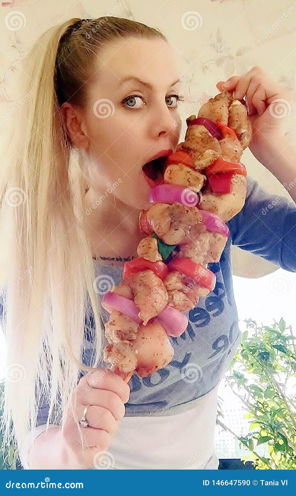 Trevlig flicka med stora kebaber av fegt kött av löken, peppar och olika kryddor