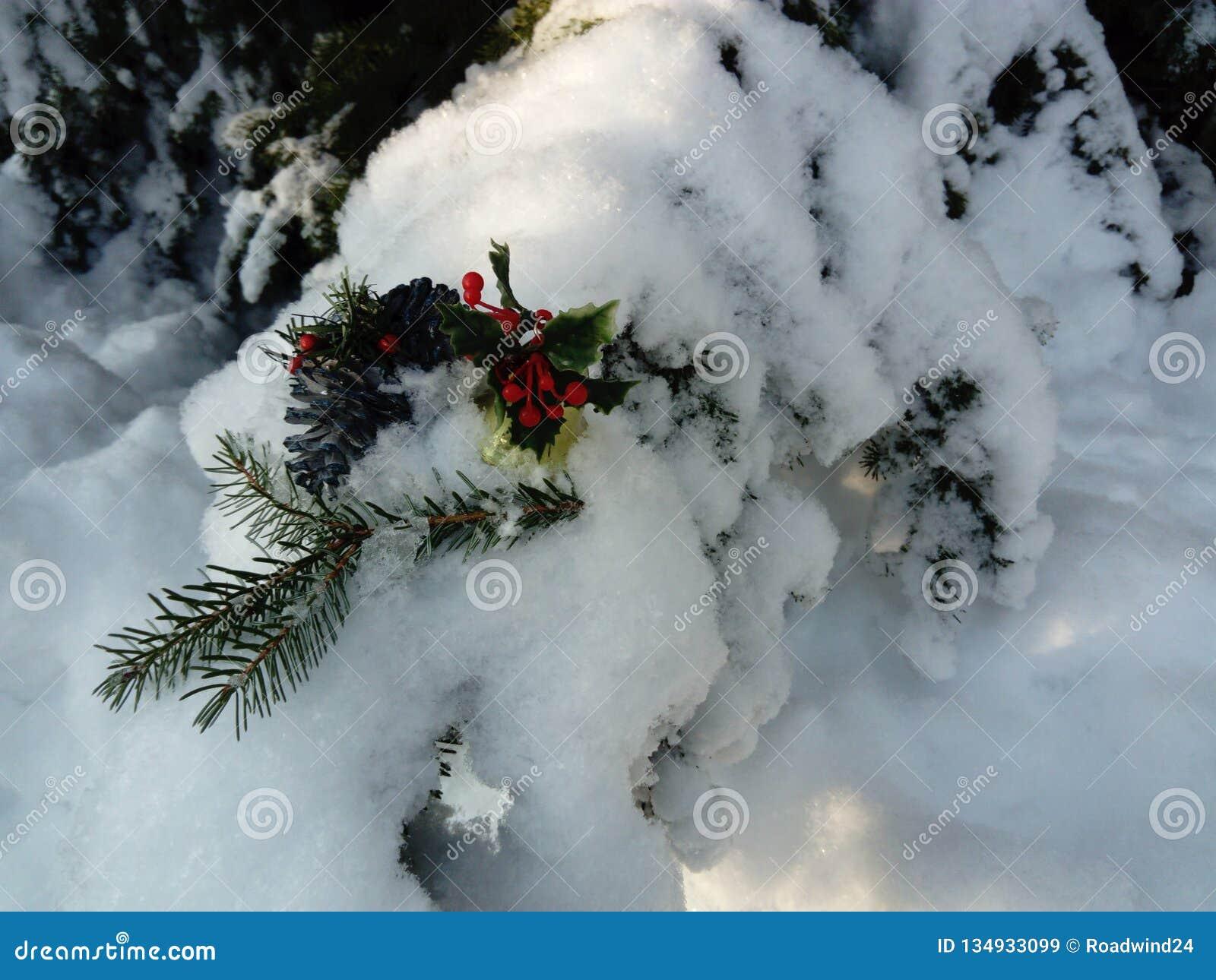 Trevlig julgarnering på snö som täckas för att sörja trädet