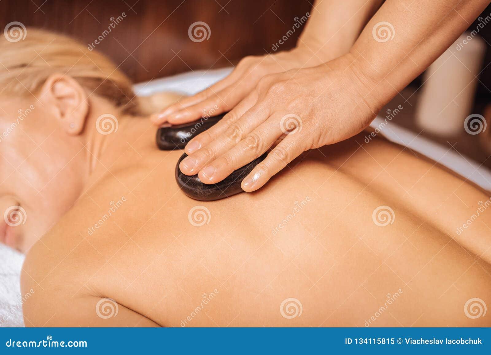 Trevlig kompetent massös som använder varma stenar för massage