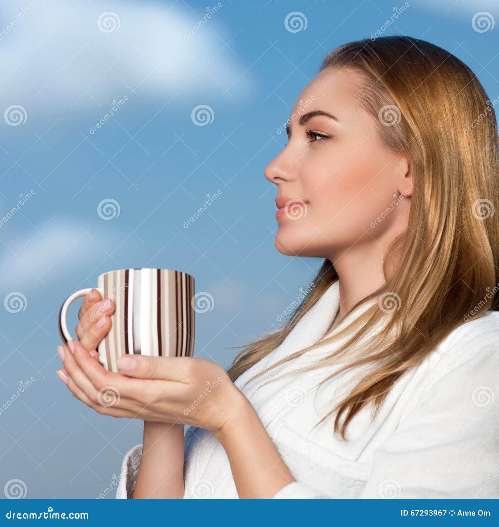 Trevlig kvinnlig med kopp te