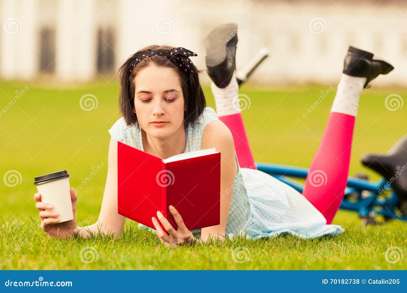 Trevlig ung kvinna som läser en bok och tycker om ett kaffe