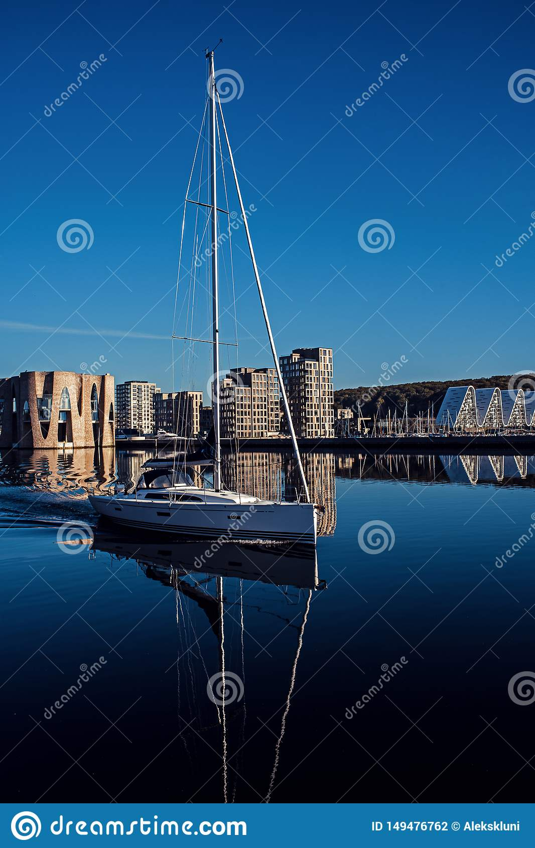 Trevlig vit segla yacht Landskap av byggnader n?ra pir Yacht p? bakgrunden av nybyggen