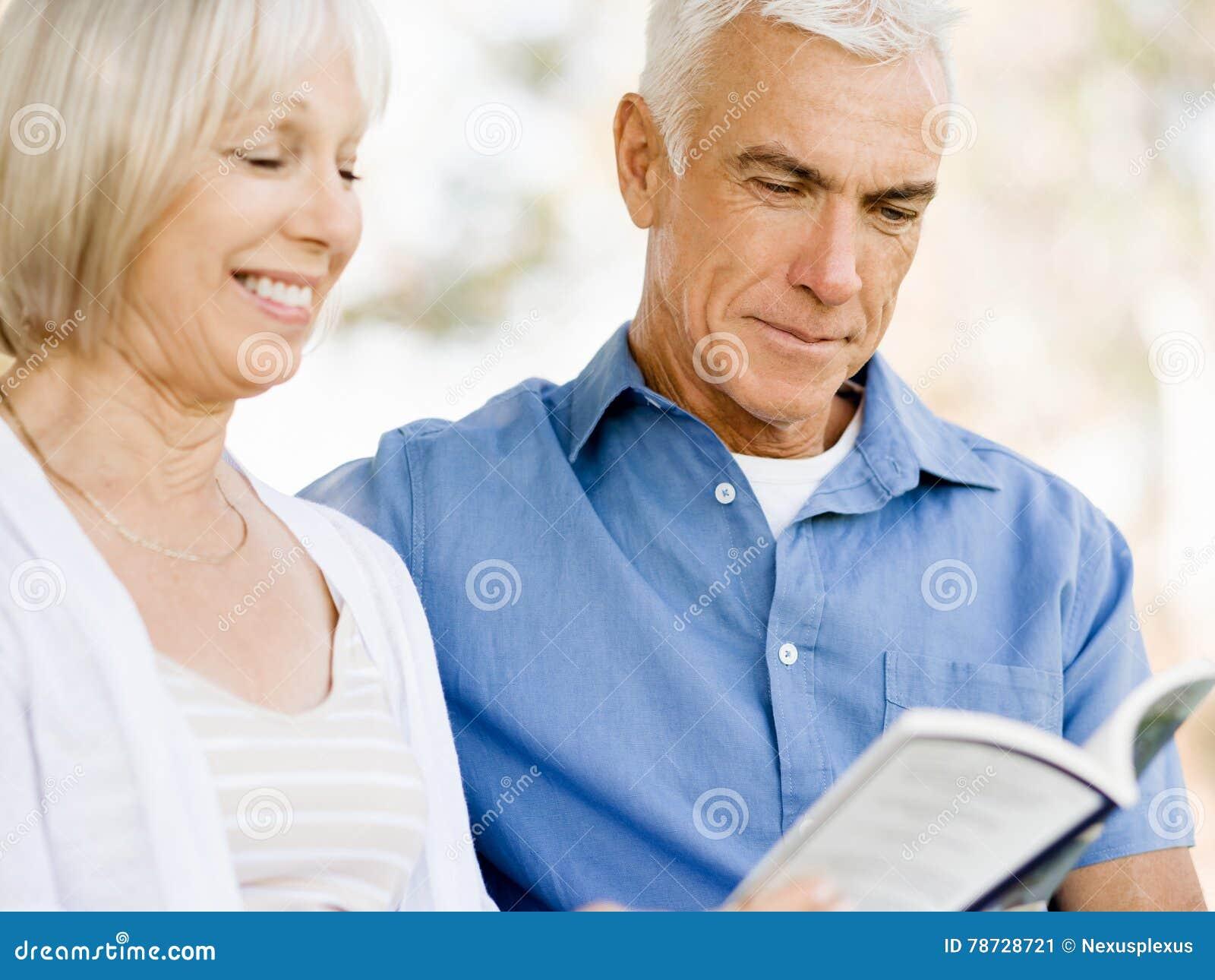 Trevligt åldringparsammanträde utomhus med boken