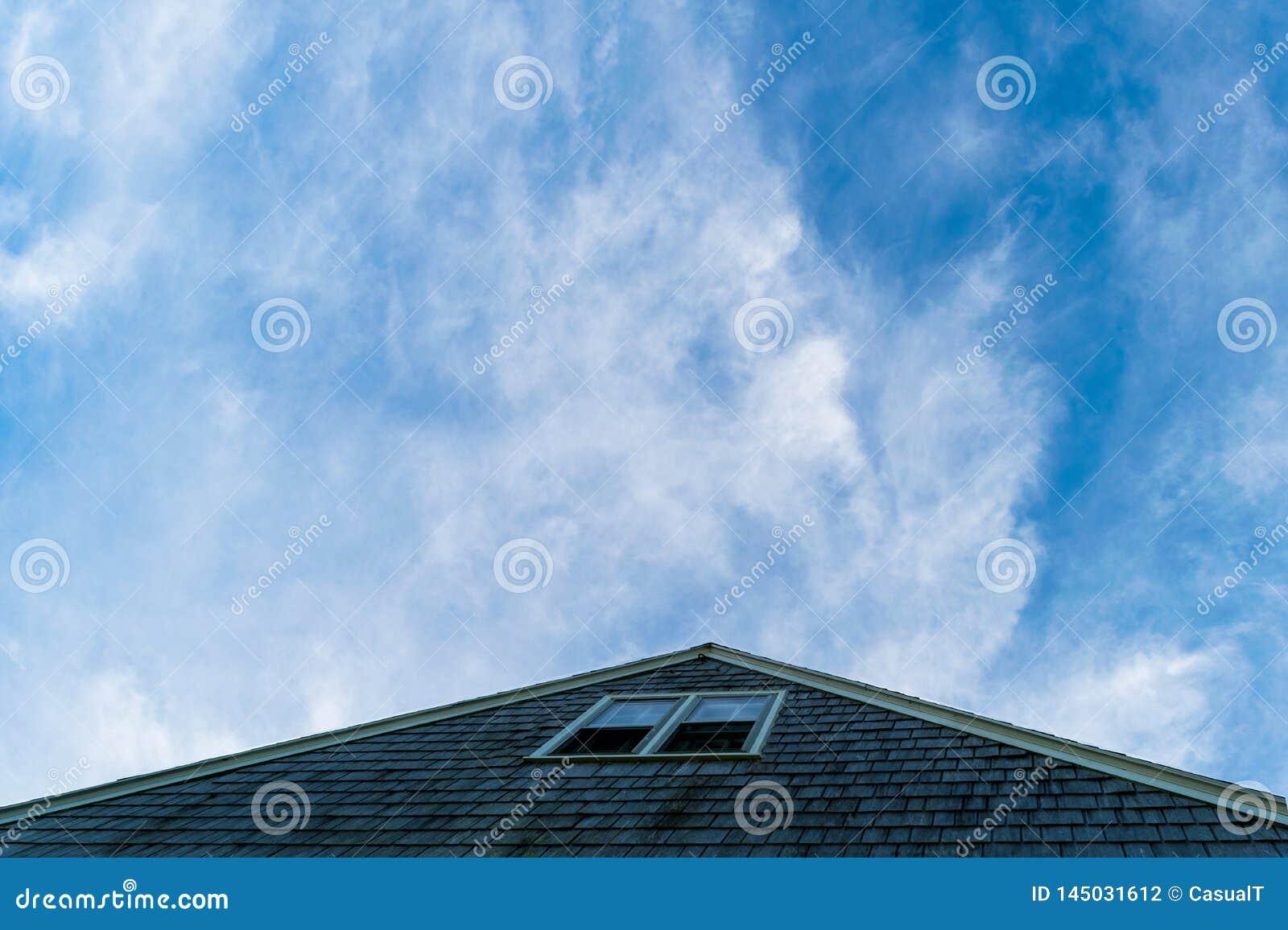 Triangulärt tak som pekar in mot en härlig blått, litet molnig himmel, kvarterö, RI