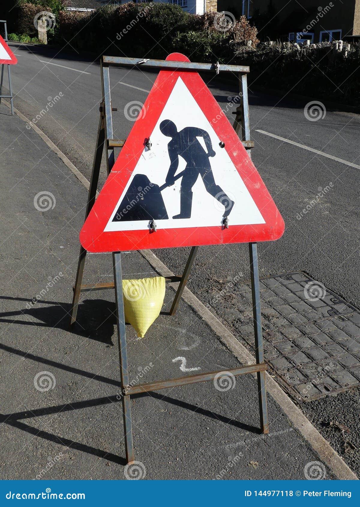 Triangulärt tecken för vägarbeten på metallram vid vägrenen