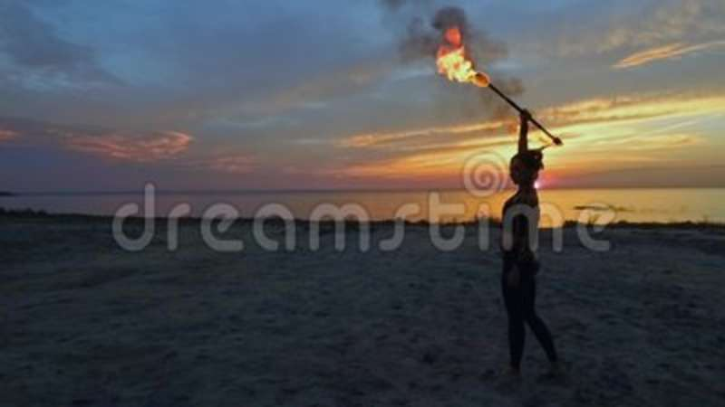 Beautiful woman is holding fire stick abowe her head at the beach