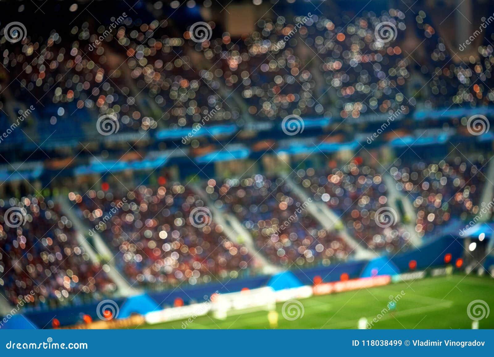 Tribune piene dello stadio di calcio di calcio con le luci Fondo vago fuoco molle
