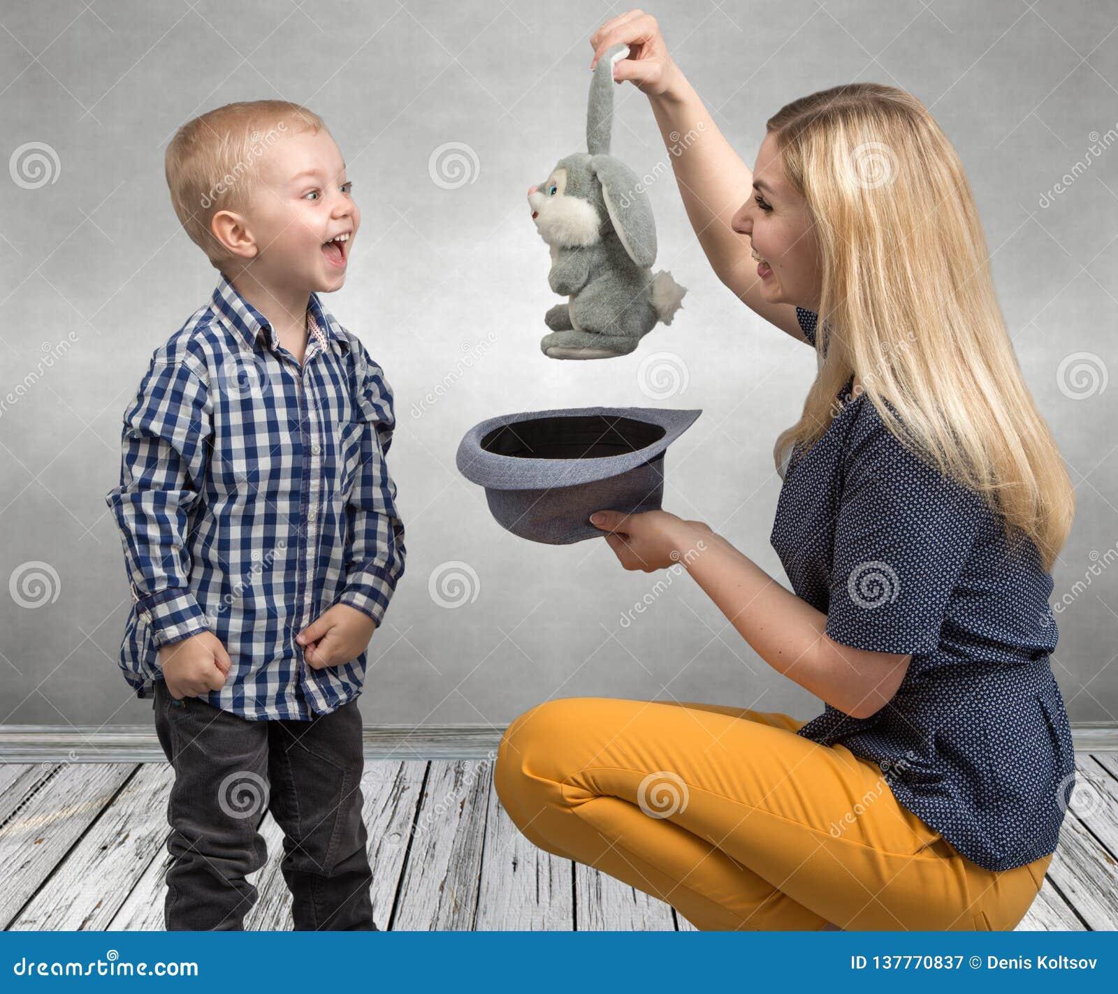 Trick med en kanin En ung moder visar att magiska trick för pysen oavbrutet tjata i hatten Familjvänskapsmatch, underhållning