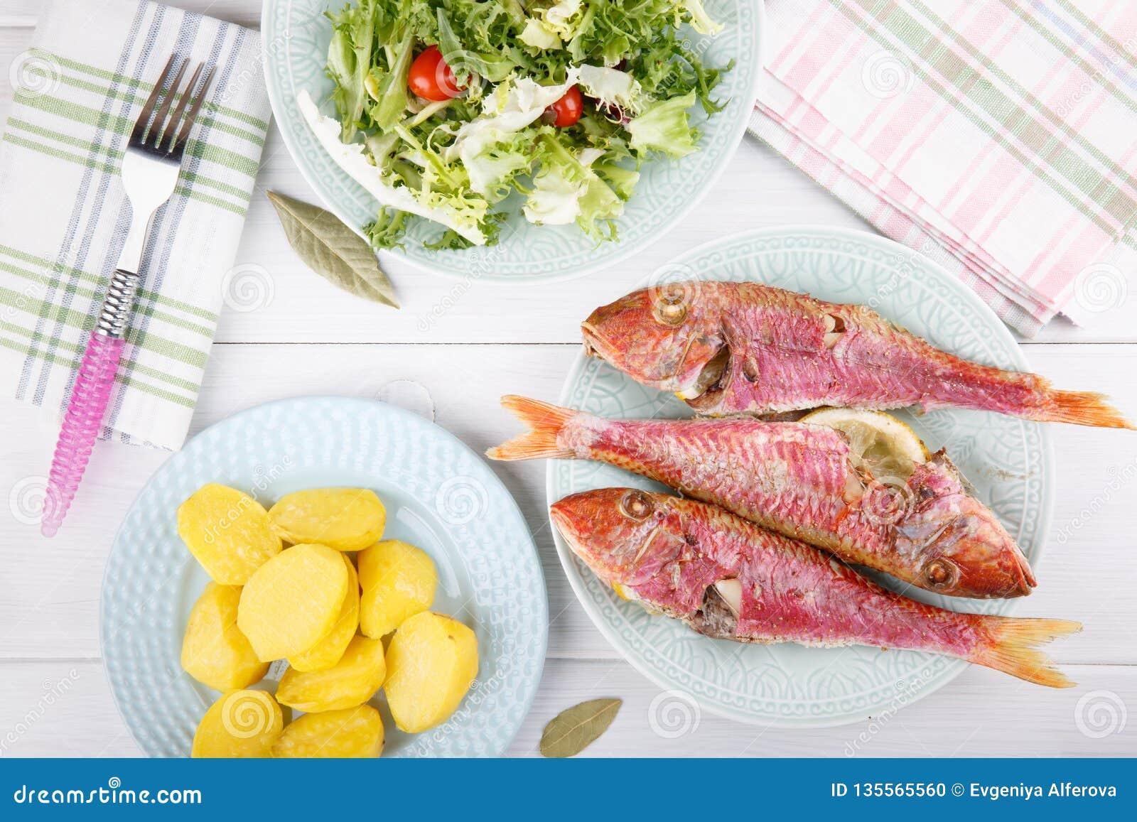 Triglia cotta servita con le patate e l insalata verde bollite