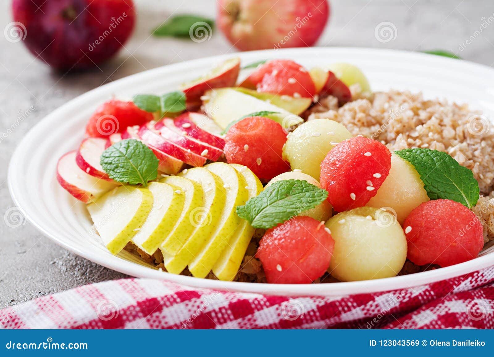 Trigo mourisco ou papa de aveia com melão, a melancia, a maçã e a pera frescos