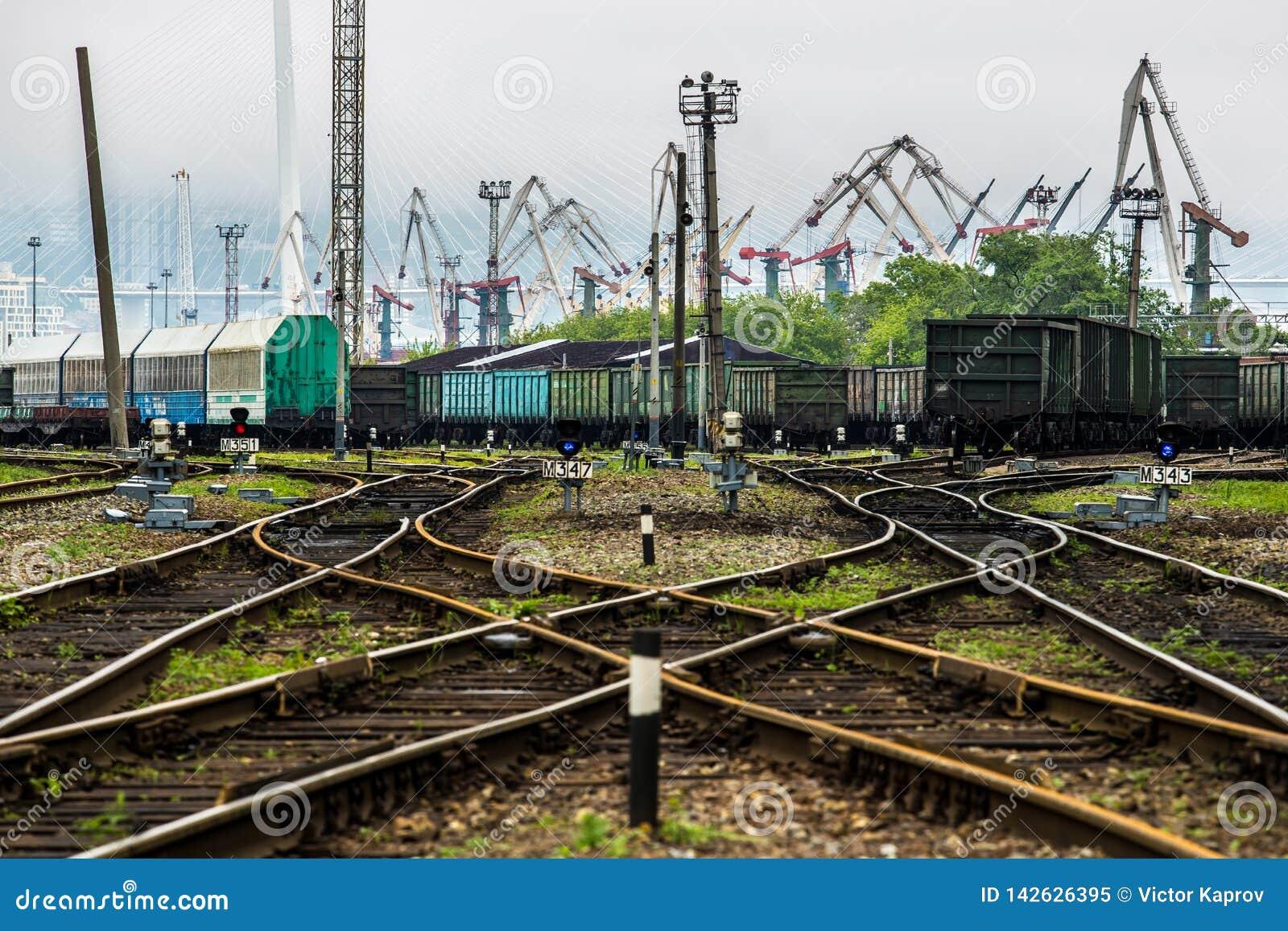 Trilhas de estrada de ferro e o porto no fundo