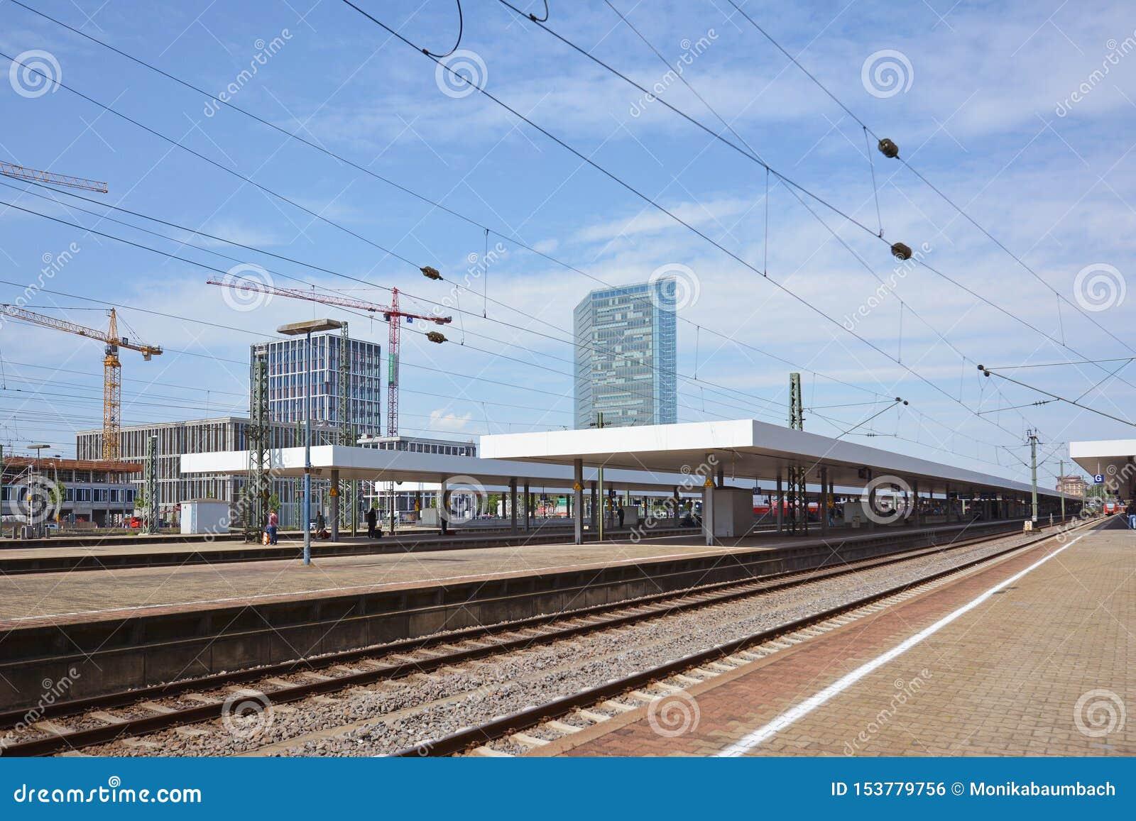 Trilhas e plataformas do estação de caminhos de ferro principal de Mannheim no dia de verão com céu azul