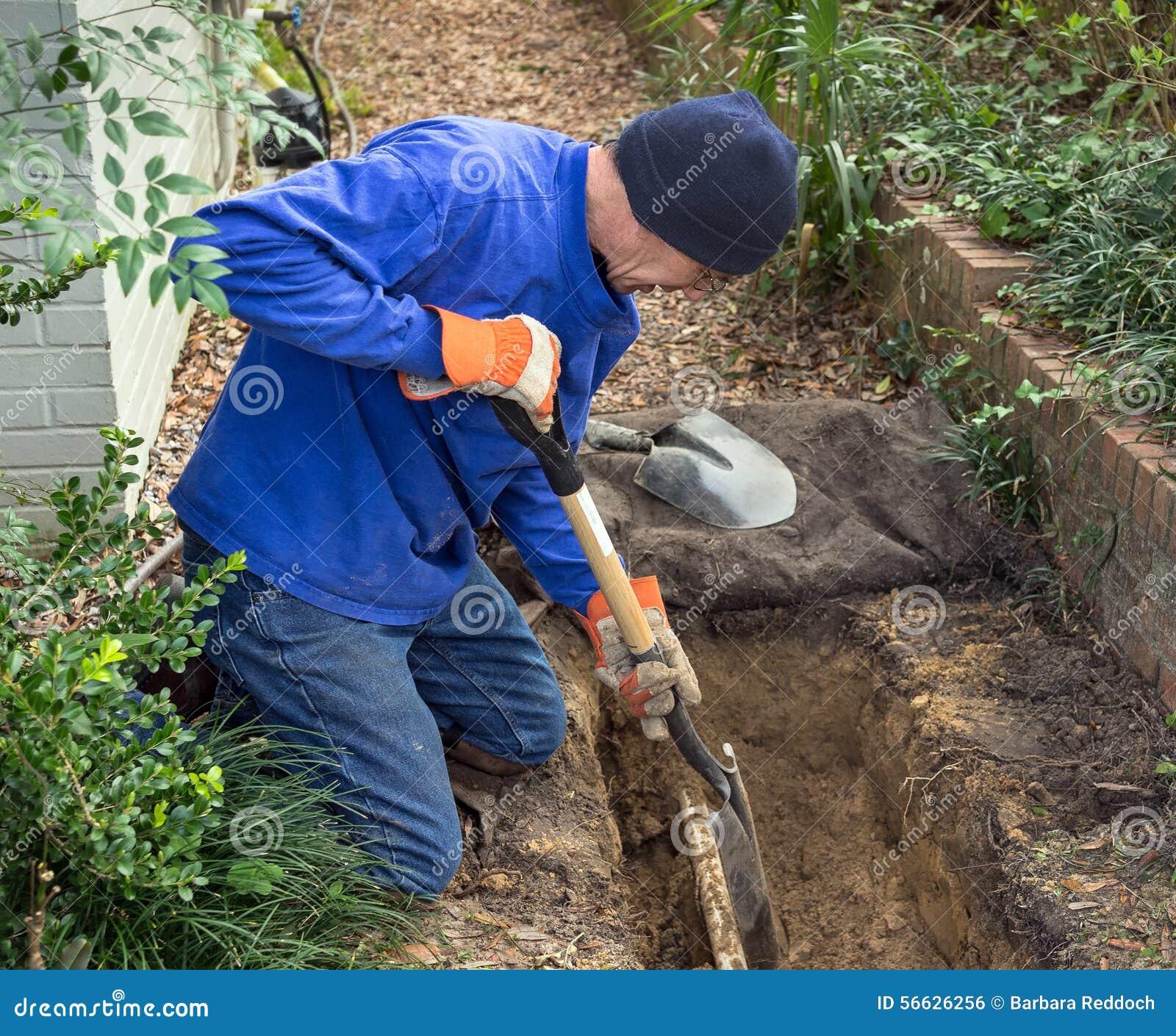 A trincheira de escavação do homem para substituir a linha tubulações e gramado do esgoto polvilha