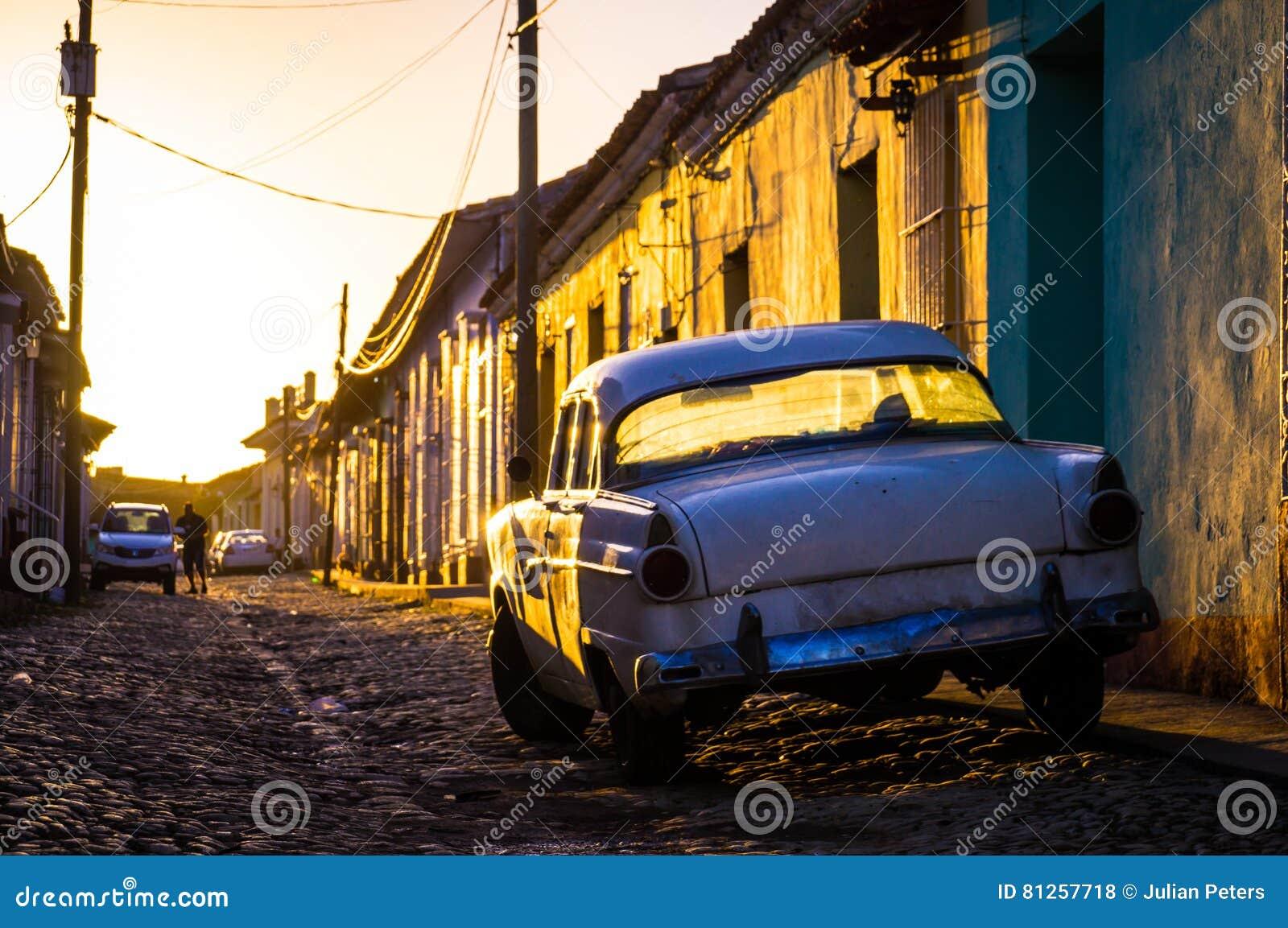 Trinidad, Kuba: Straße mit Oldtimer bei Sonnenuntergang