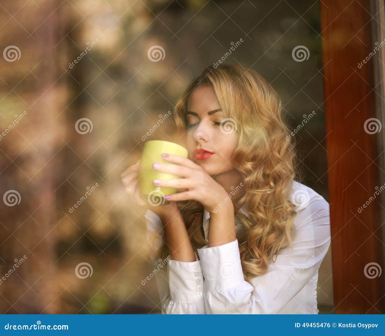 Trinkender Kaffee der Frau zuhause, das Aroma des Getränkes genießend
