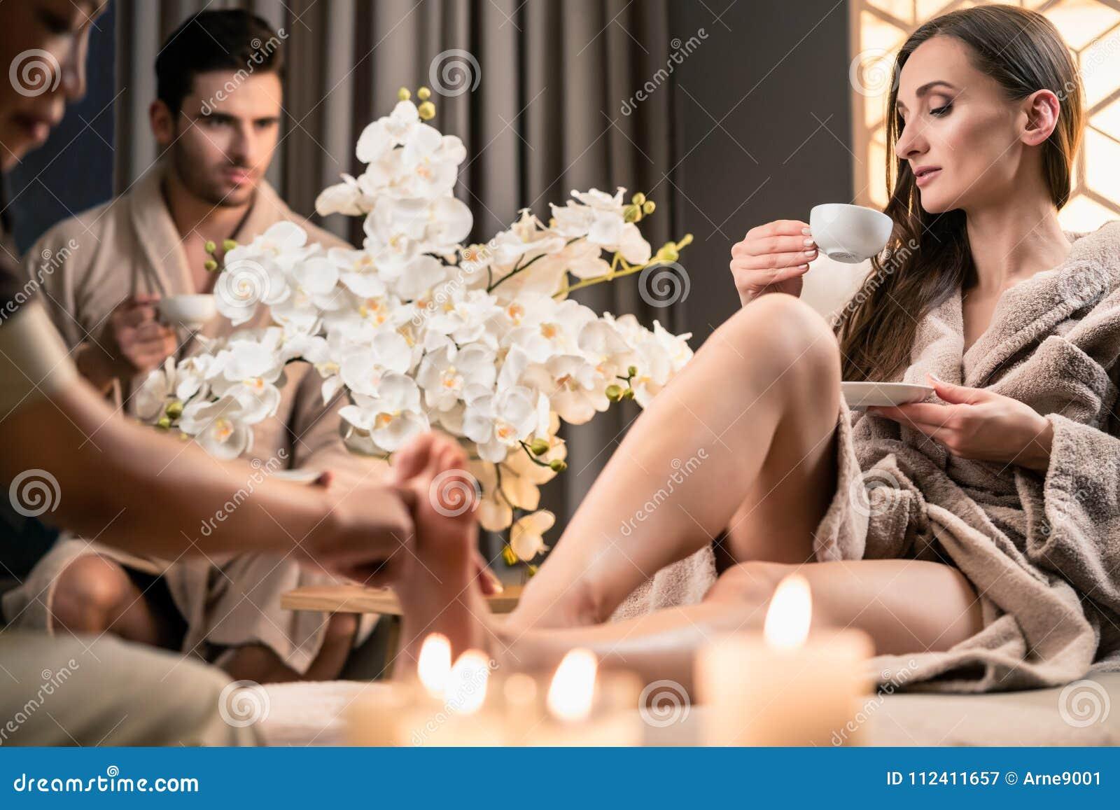 Trinkender Tee der Schönheit während der therapeutischen Fußmassage