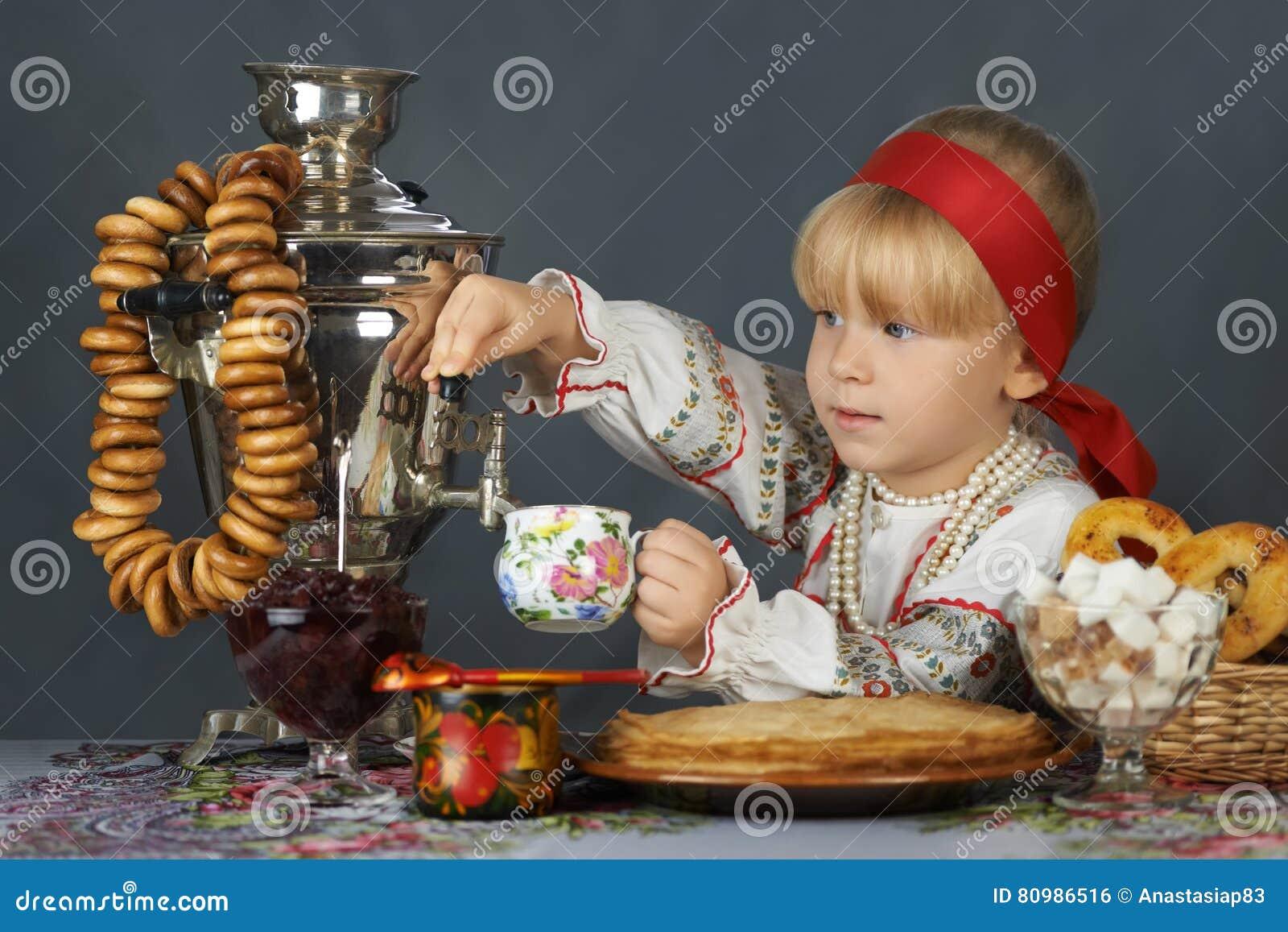 Trinkender Tee des kleinen Mädchens im traditionellen russischen sarafan und im Hemd