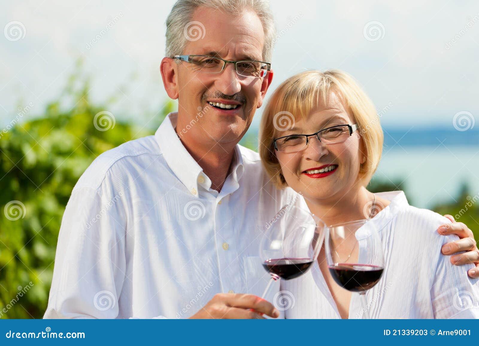 Trinkender Wein der glücklichen Paare in See am Sommer