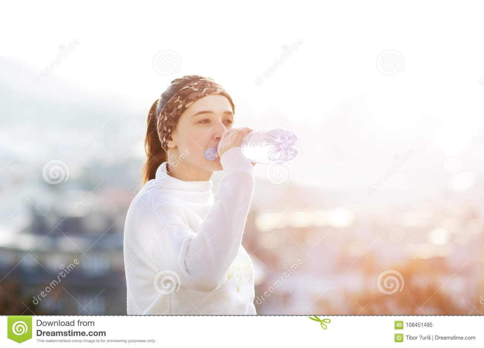 Trinkwasser der Frau während eines Betriebs Herbst Kühles Wetter Rüttelnde Frau in einer Stadt während eines Winters Sonniger Tag