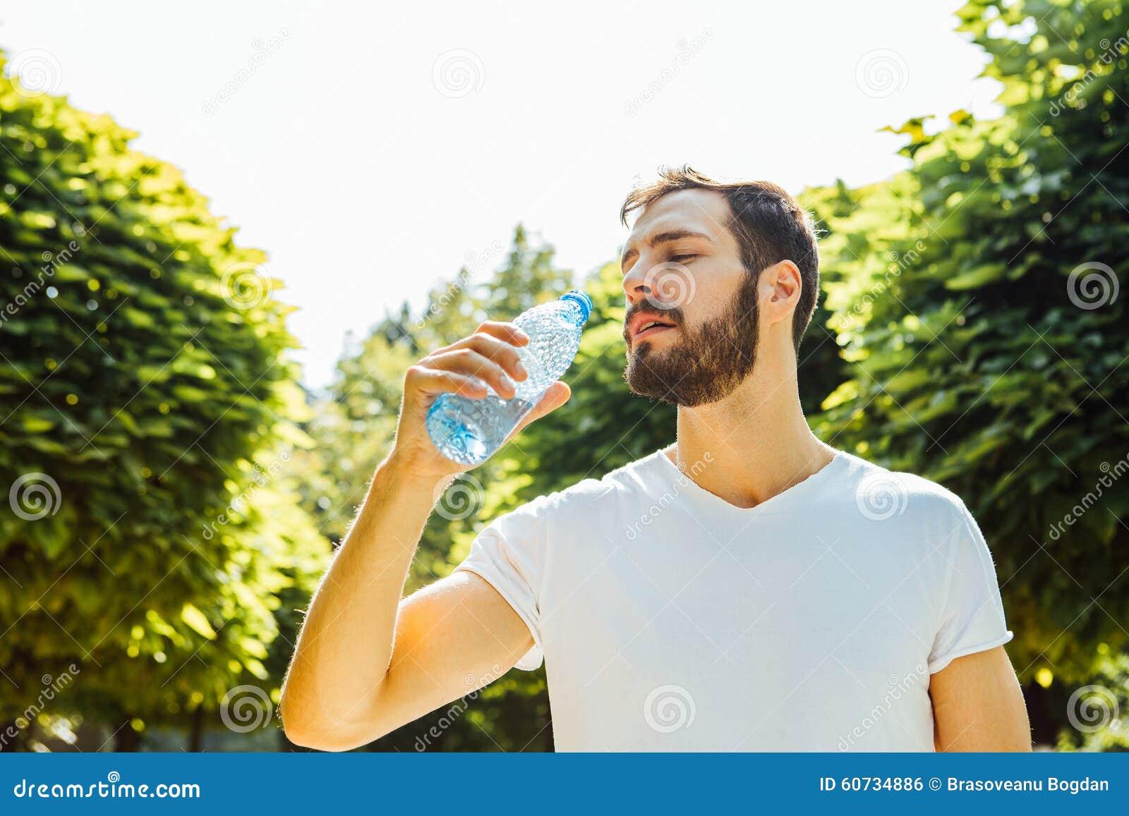 Trinkwasser des erwachsenen Mannes von einer Flasche draußen