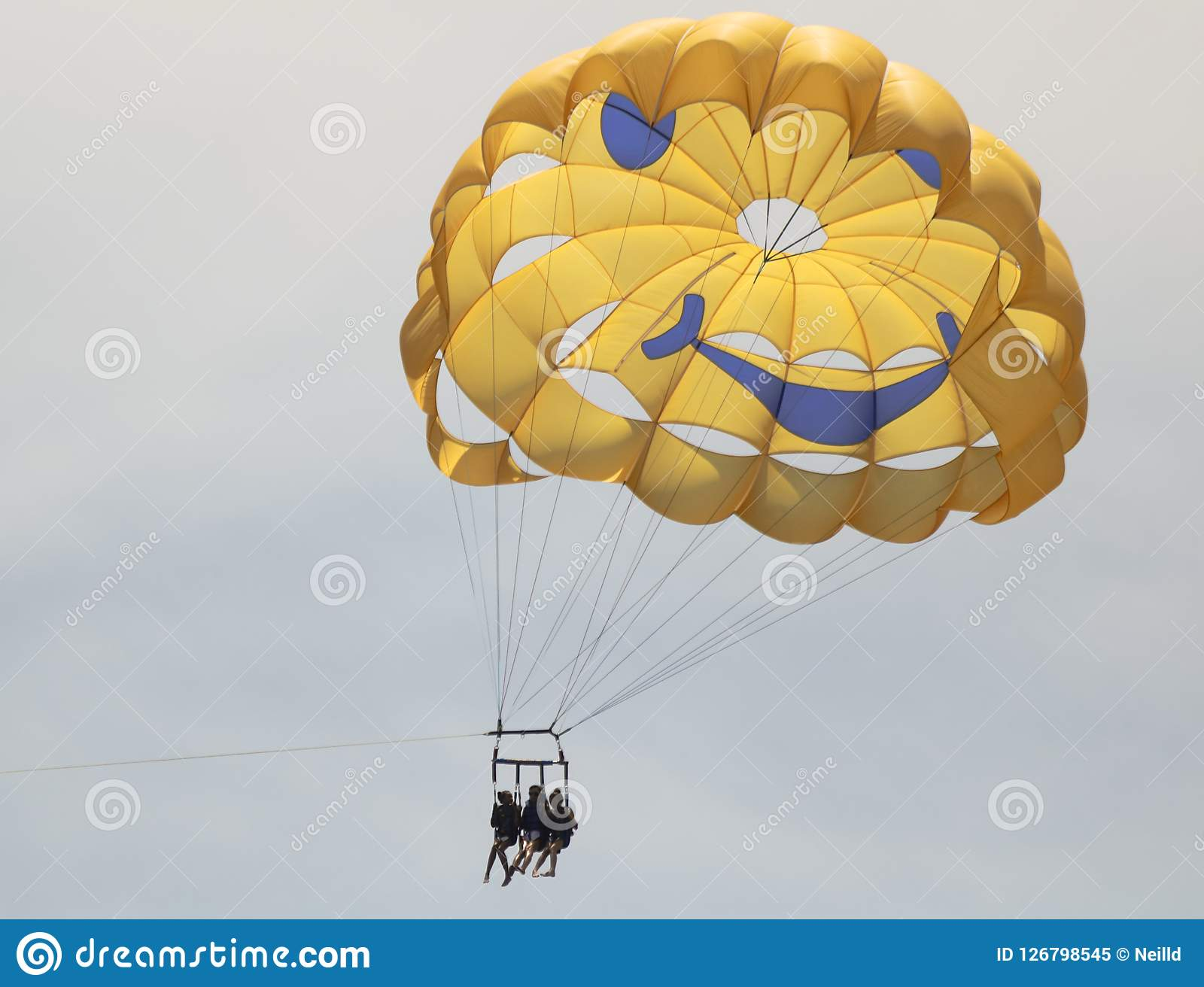 A Trio Parasailing Above Lahaina Harbor, West Maui, Hawaii. A Trio of Girls Suspended from a Happy Face Parasail Above Lahaina Harbor, West Maui, Hawaii Royalty Free Stock Photo