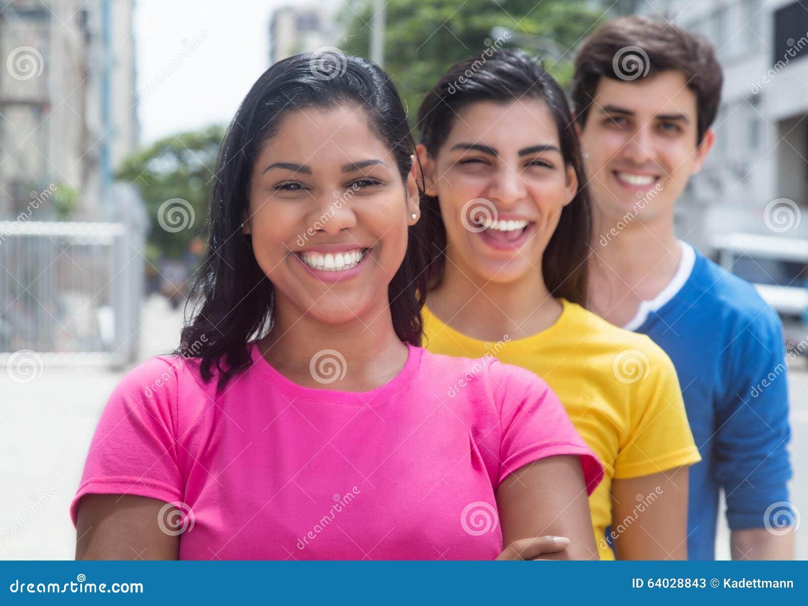 Triojongeren in kleurrijke overhemden die zich in lijn bevinden