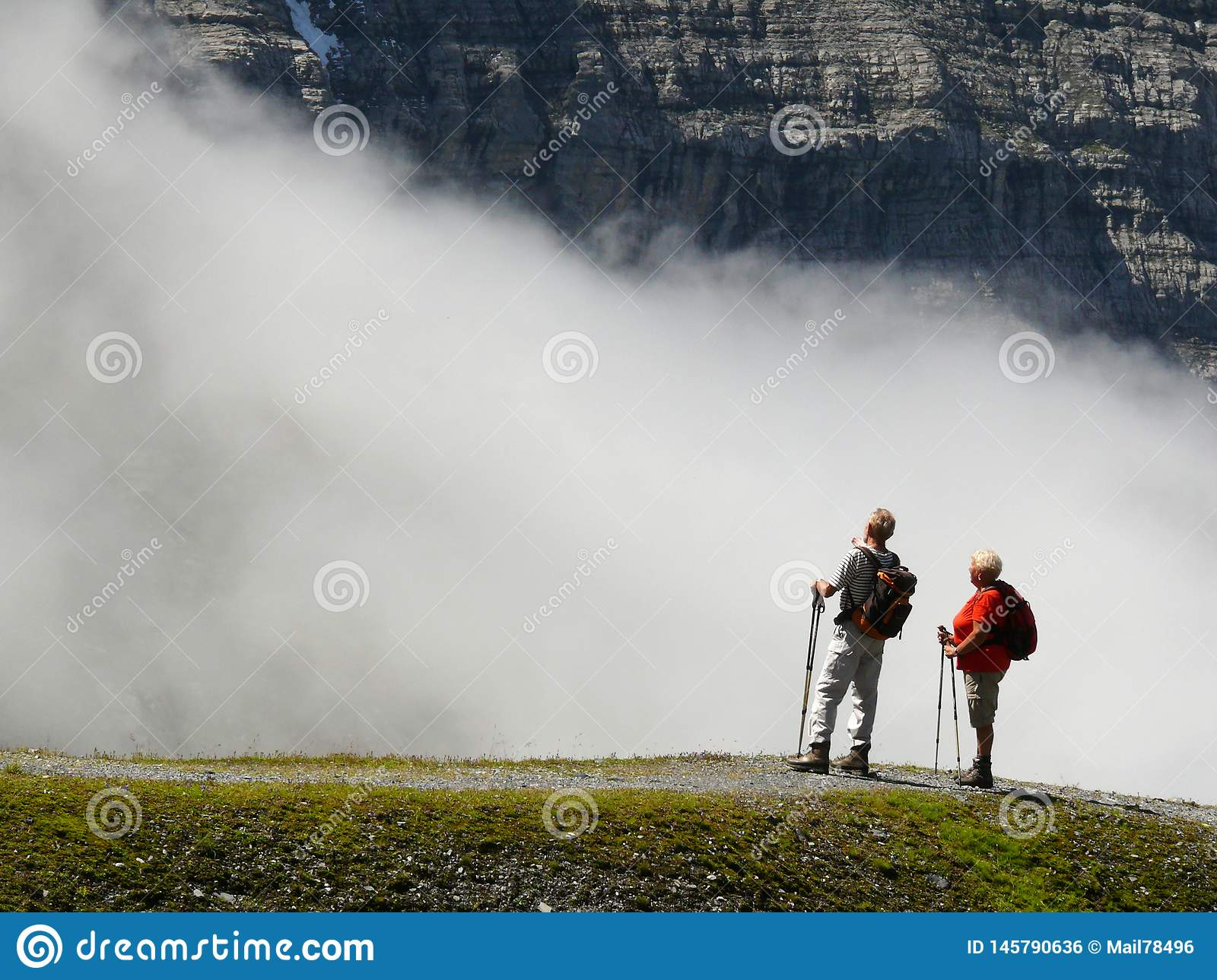 Wengen, Switzerland. 08/17/2010. Two hikers in the high mountains admire the landscape