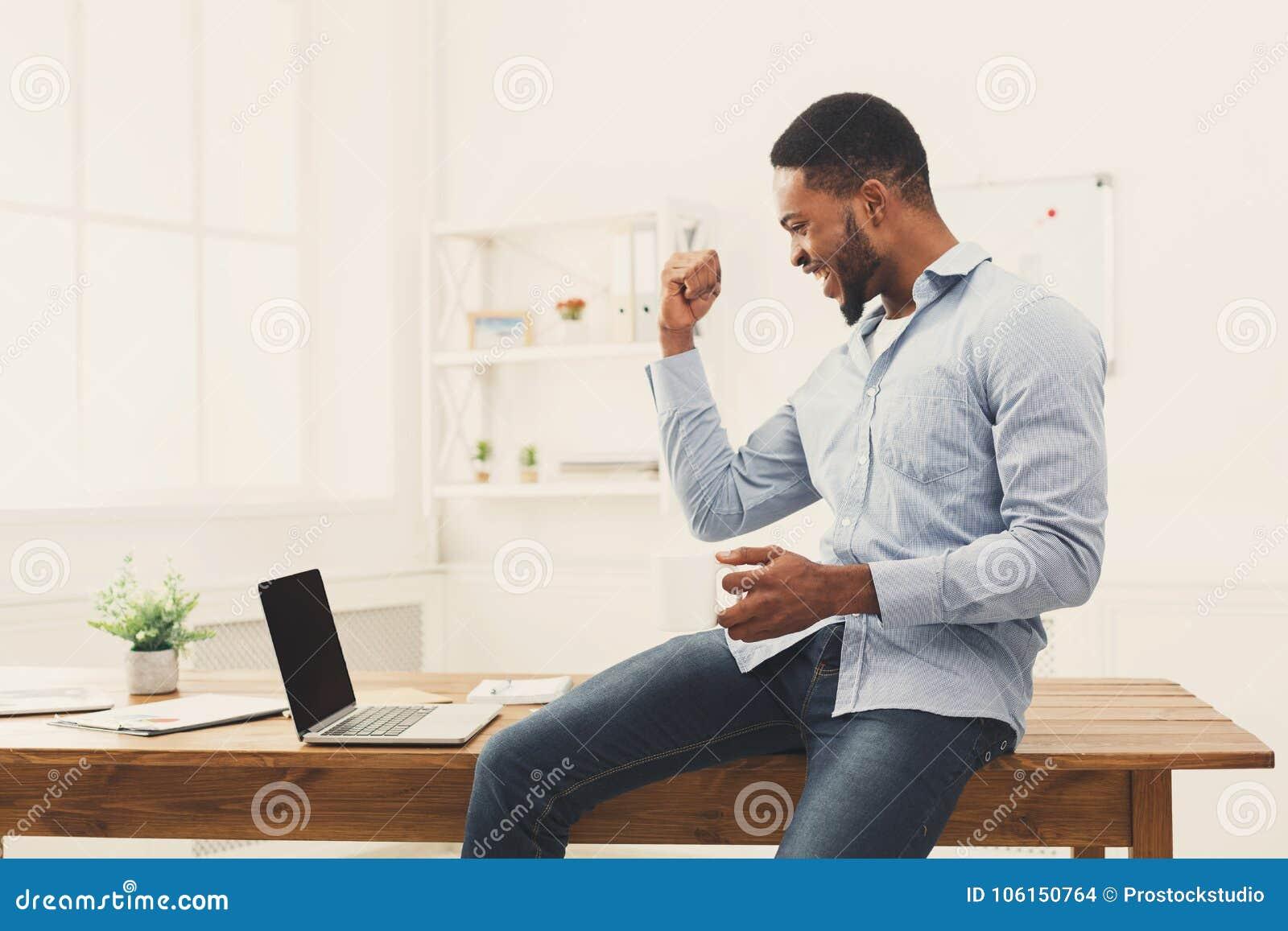 Triunfo feliz del hombre de negocios Ganador, hombre negro en oficina