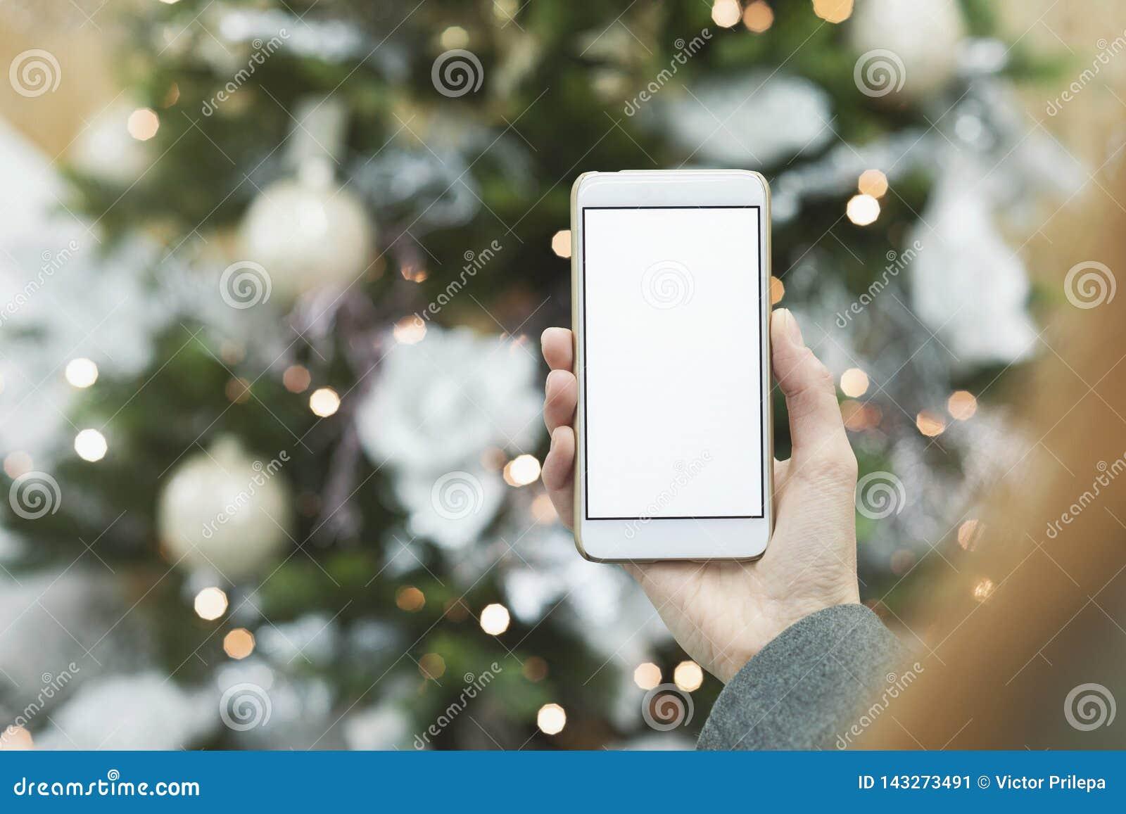 Trocista acima do smartphone na mão da menina no fundo da árvore de Natal com uma decoração festiva