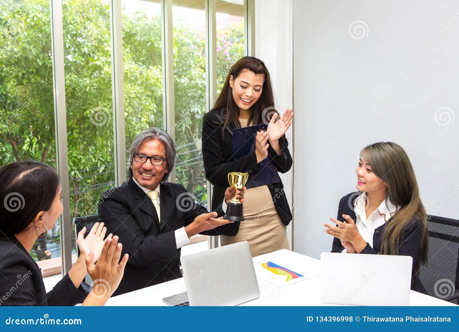 Troféu de vencimento da equipe do negócio no escritório Homem de negócios com os trabalhos de equipe na concessão e no troféu mos