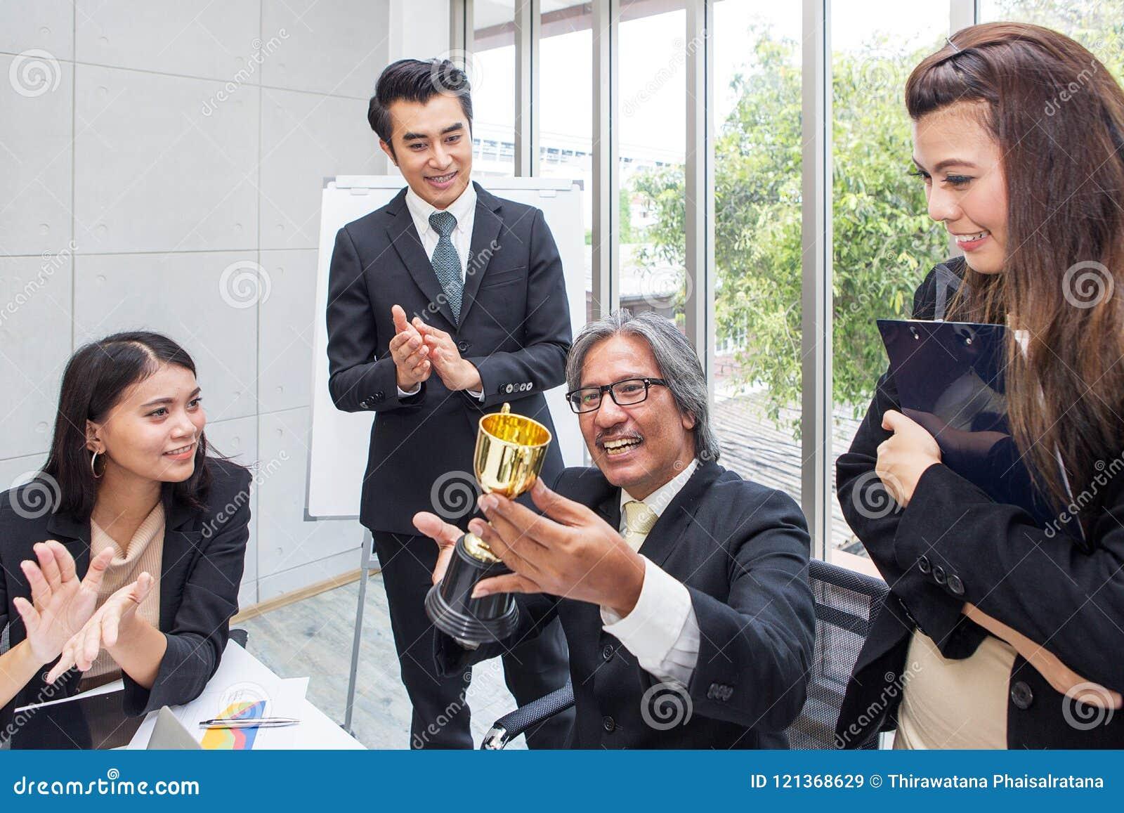 Troféu de vencimento da equipe do negócio no escritório Homem de negócios com te