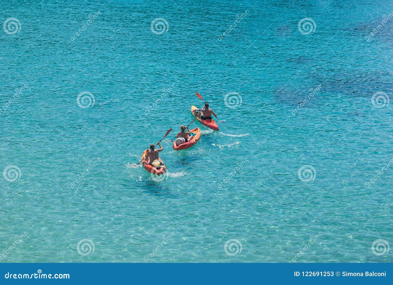 Trois adultes sur un rouge kayaks en mer