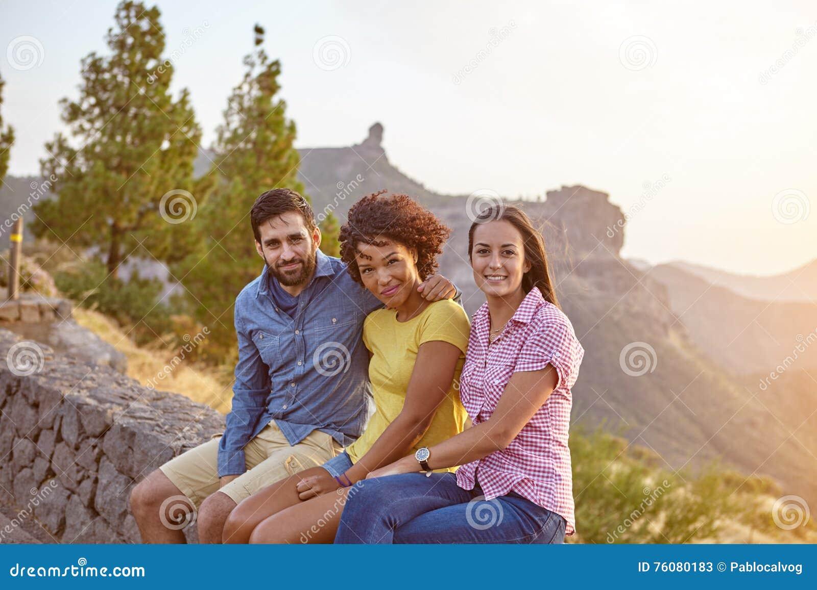 Trois amis s asseyant sur un mur en pierre