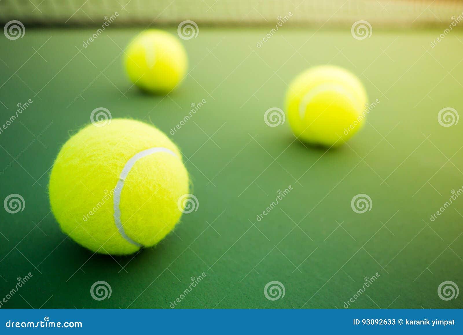 Trois balles de tennis sur la cour dure verte