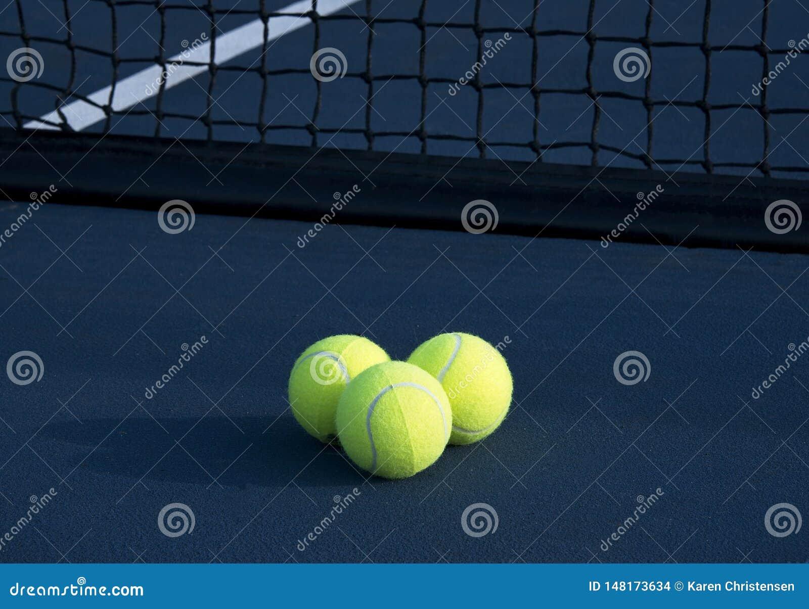 Trois balles de tennis sur un court de tennis