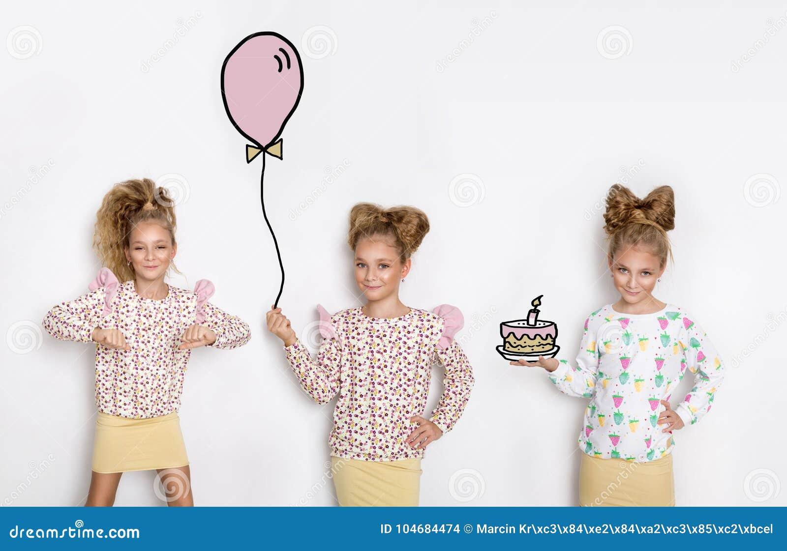 Trois belles petites filles renversantes avec de longs cheveux blonds se tenant sur un fond et blancs d entre eux prises un ballo