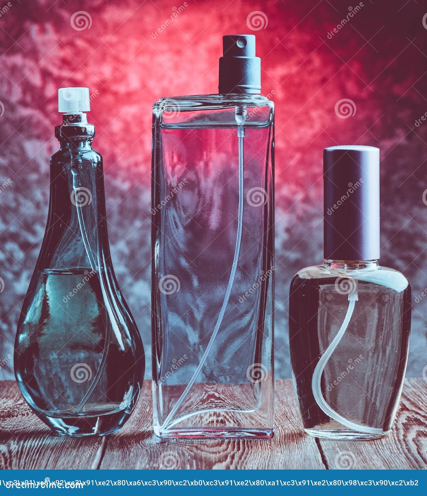 Trois bouteilles différentes de parfum sur une étagère en bois