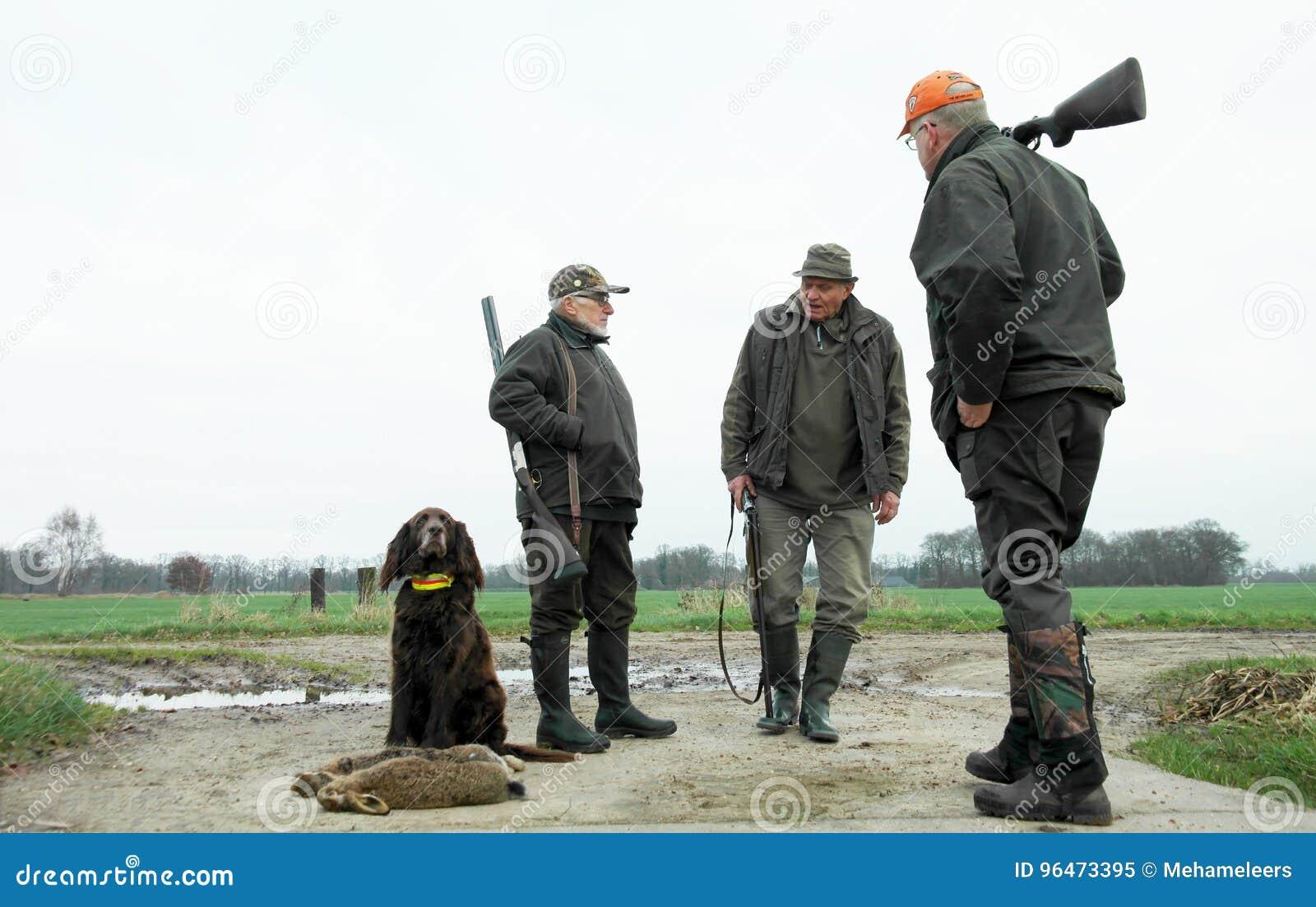 Trois chasseurs et chiens masculins avec des lièvres Point de vue inférieur Zone rurale Saison de l hiver Chien de chasse fier se