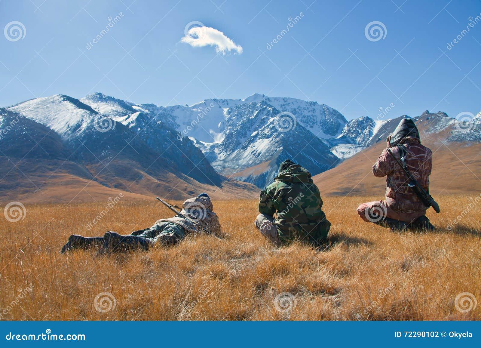 Trois chasseurs regardant par des jumelles en montagnes de Tien Sh