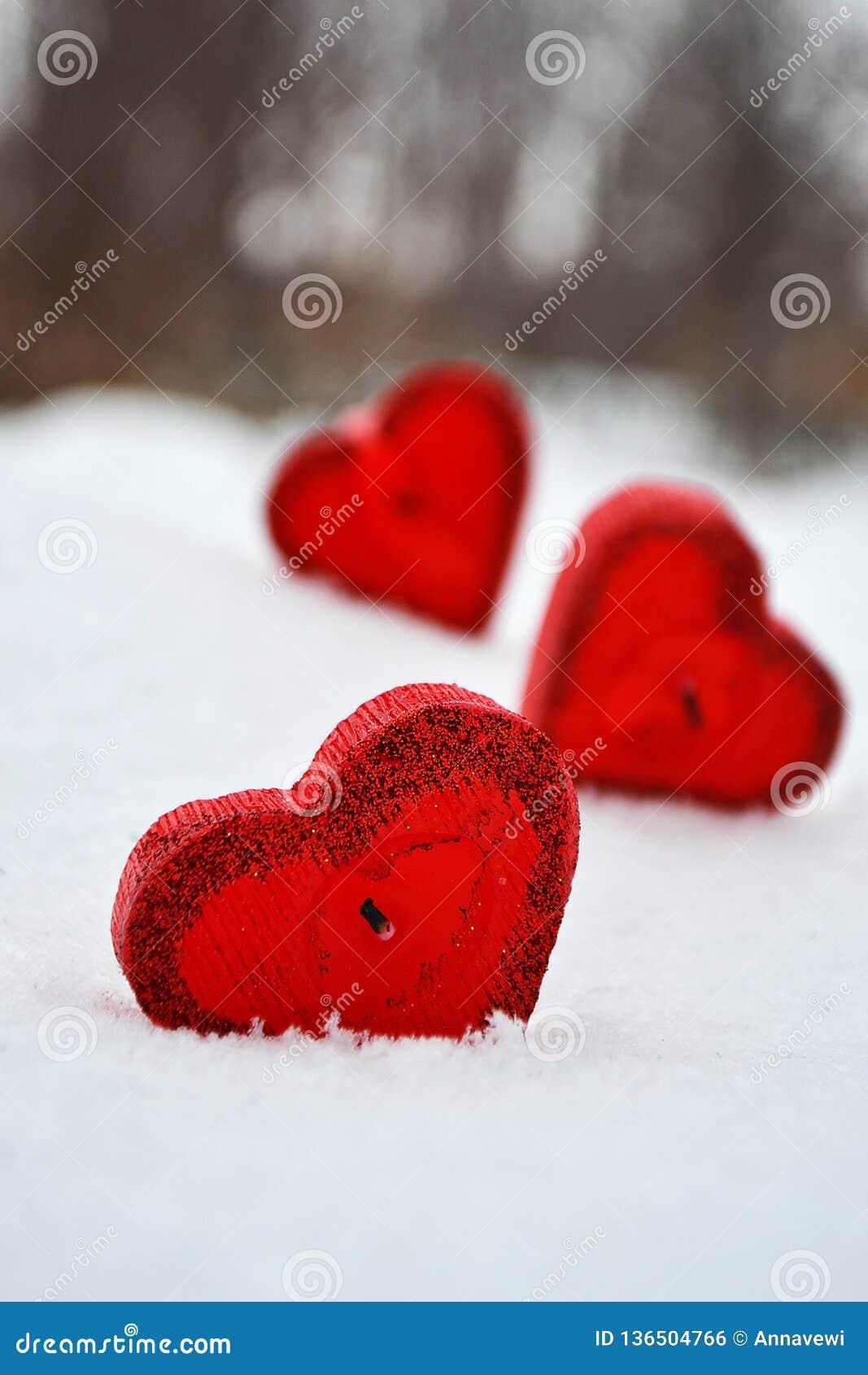Trois coeurs rouges - bougies sur la neige blanche, un cadeau pour aimé