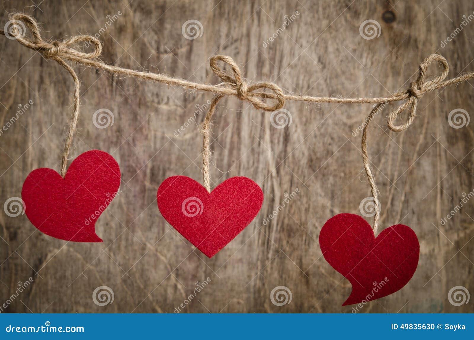 Trois coeurs rouges de tissu accrochant sur la corde à linge