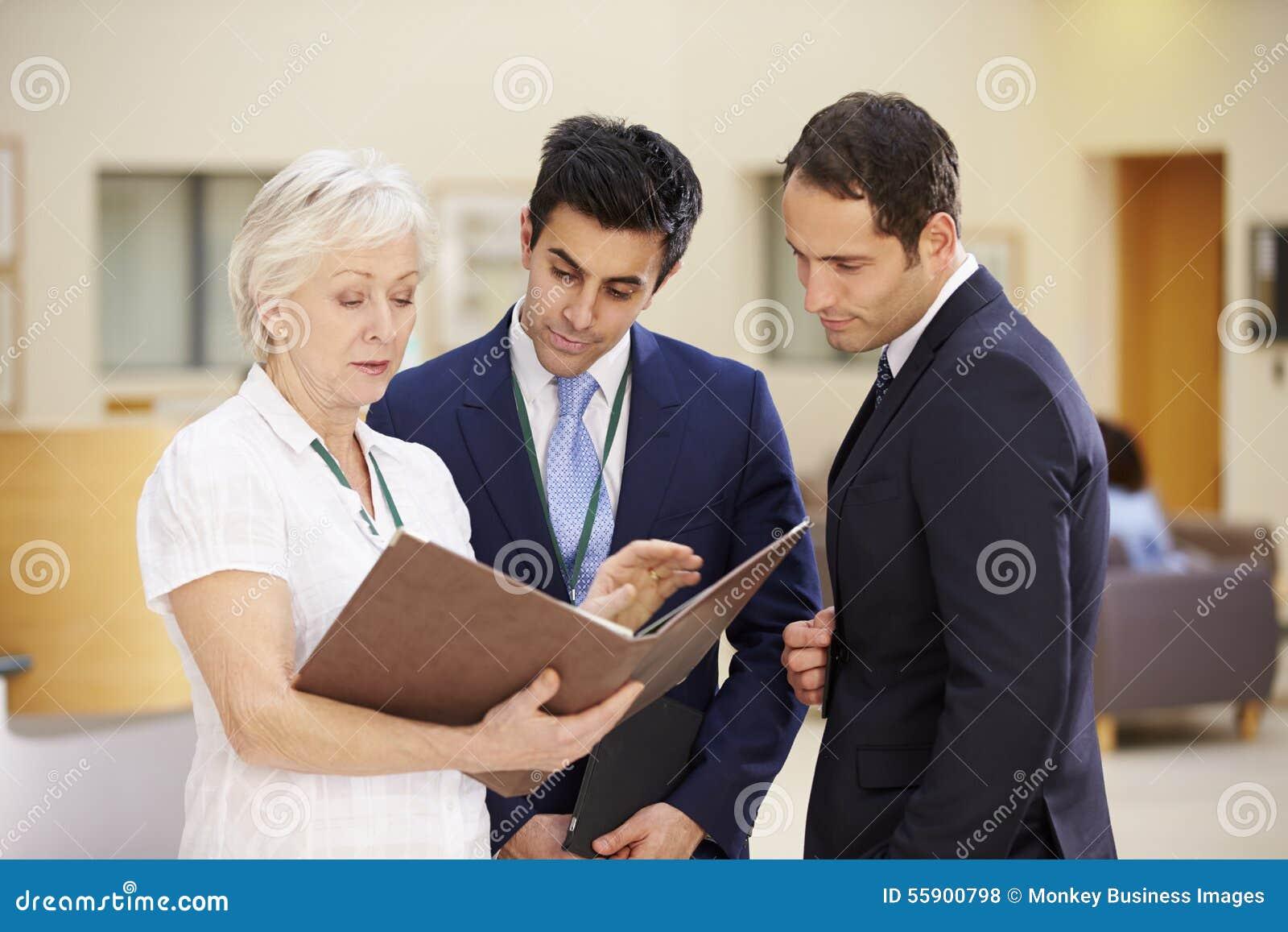 Trois conseillers discutant les notes patientes dans l hôpital