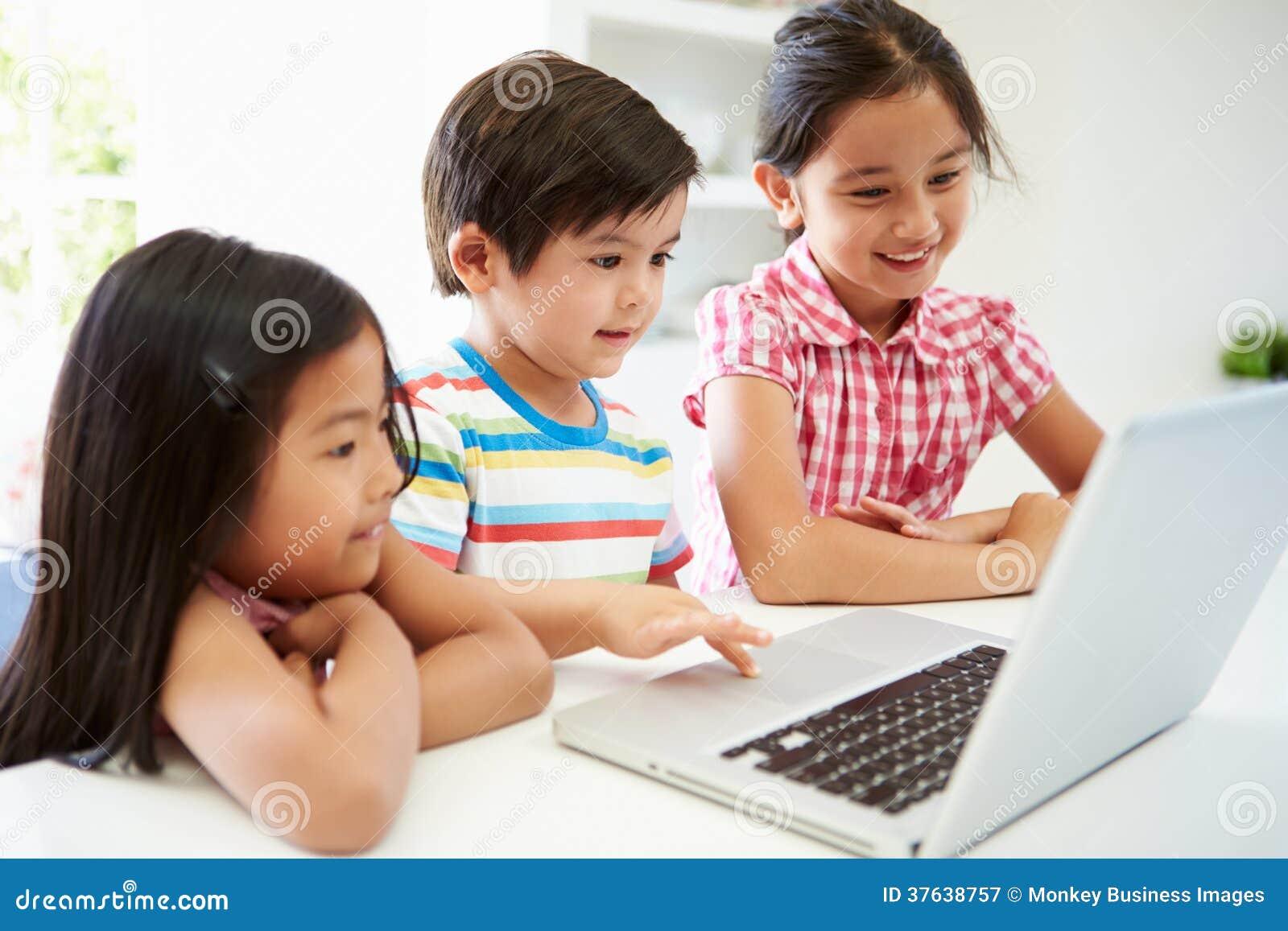 Trois enfants asiatiques à l aide de l ordinateur portable à la maison