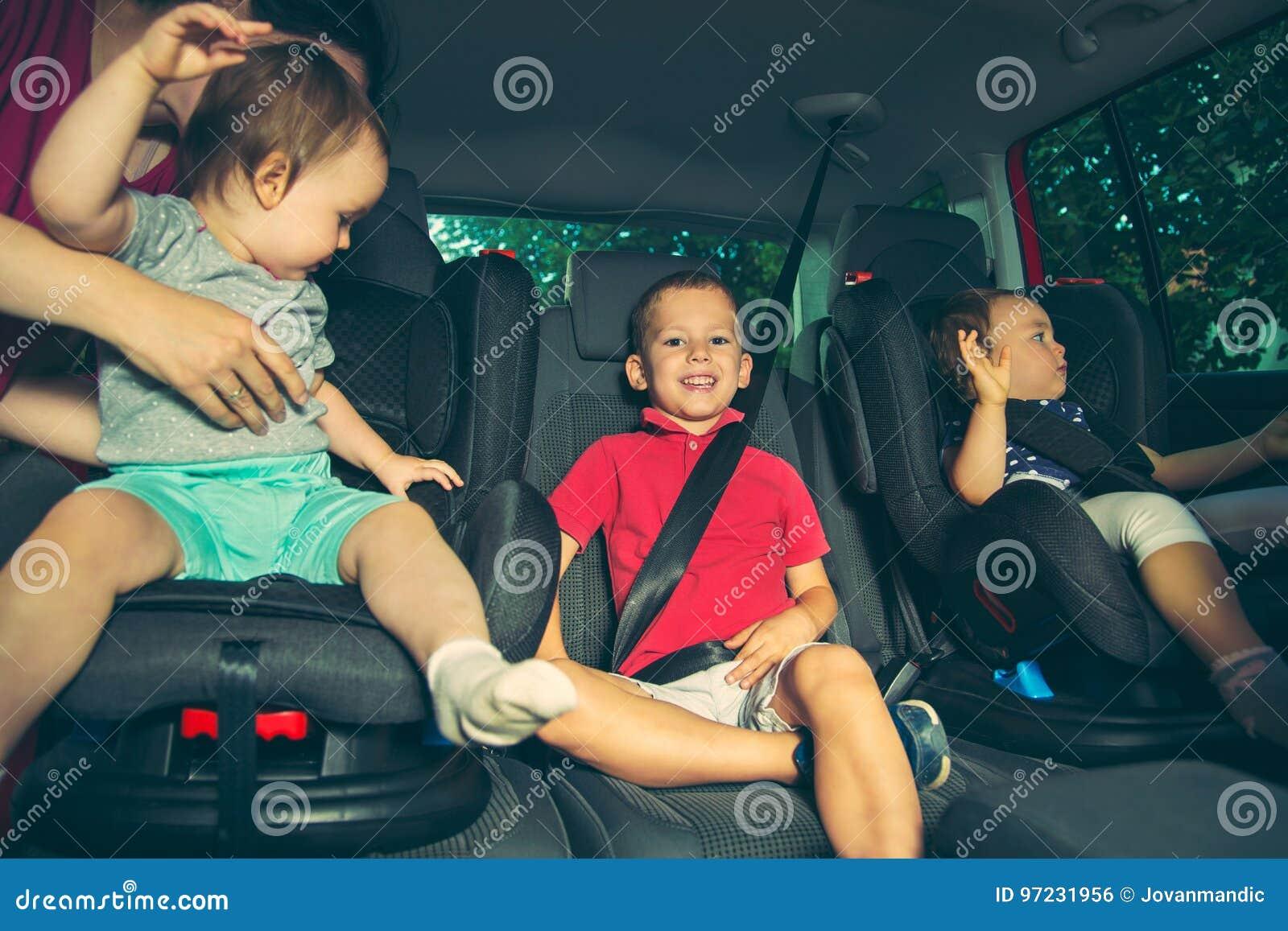 Trois enfants dans le siège de sécurité de voiture