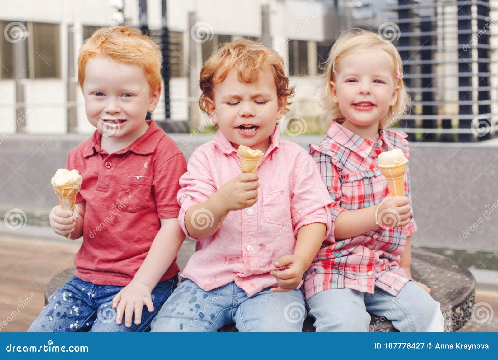 Trois enfants en bas âge drôles adorables mignons caucasiens blancs d enfants s asseyant ensemble partageant la glace